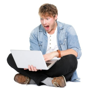 man staring excitedly at computer screen